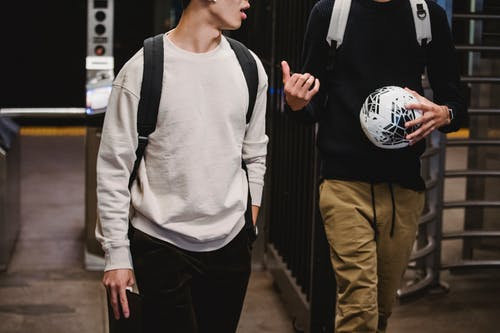 Crop young male friends wearing casual clothes with backpacks and soccer ball walking in modern underground station and chatting