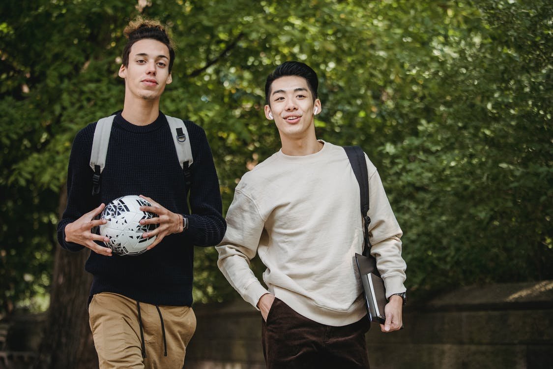 Positive young multiracial male students in casual clothes and backpacks walking in green park with ball and books in hands after lessons