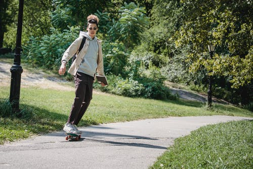 Full body of stylish active young ethnic male millennial in trendy outfit and sunglasses riding skateboard on pathway in park after studies