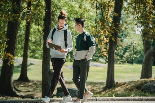 Concentrated young diverse male students strolling in park and reading notepad
