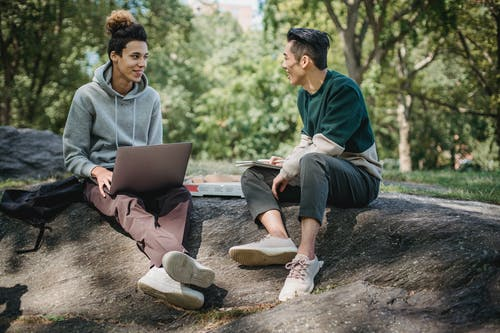 Full body of positive multiracial classmates sharing information on university assignment while browsing laptop in nature