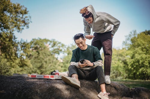 Cheerful multiethnic friends browsing smartphone while having picnic