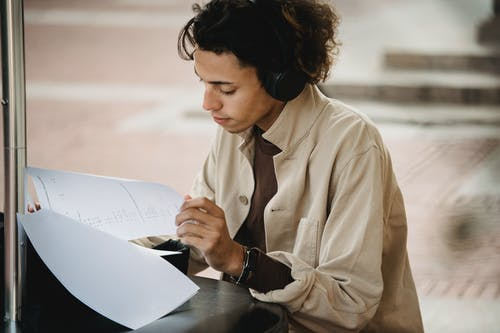 Crop focused learner doing task written on papers while using wireless headphones during studies