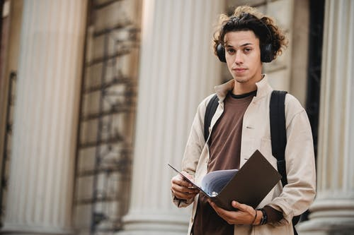 Serious student in wireless headphones with folder