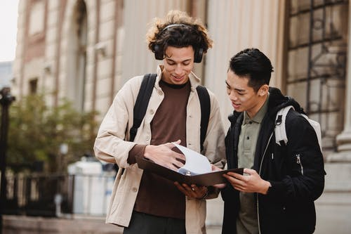 Smiling multiracial classmates turning pages of file on folder with homework task near university