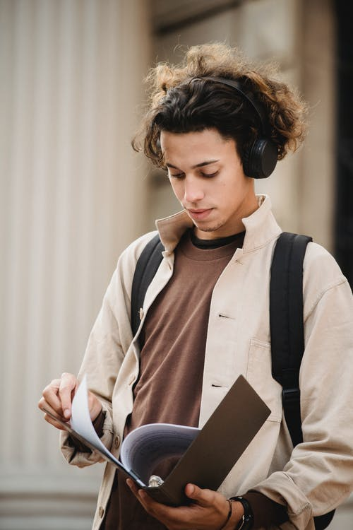 Concentrated male student looking through document with project made for university assignment while standing in wireless headphones