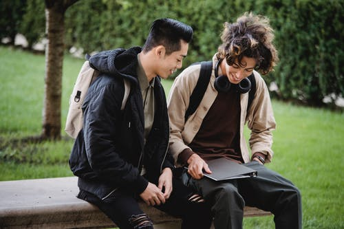 Positive multiracial friends in casual clothes with backpack and folder discussing homework assignment and smiling together
