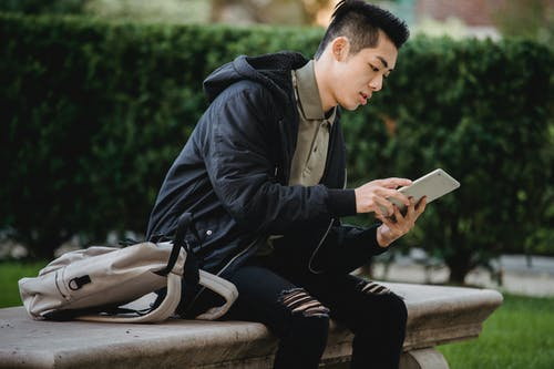 Serious ethnic student using tablet on bench