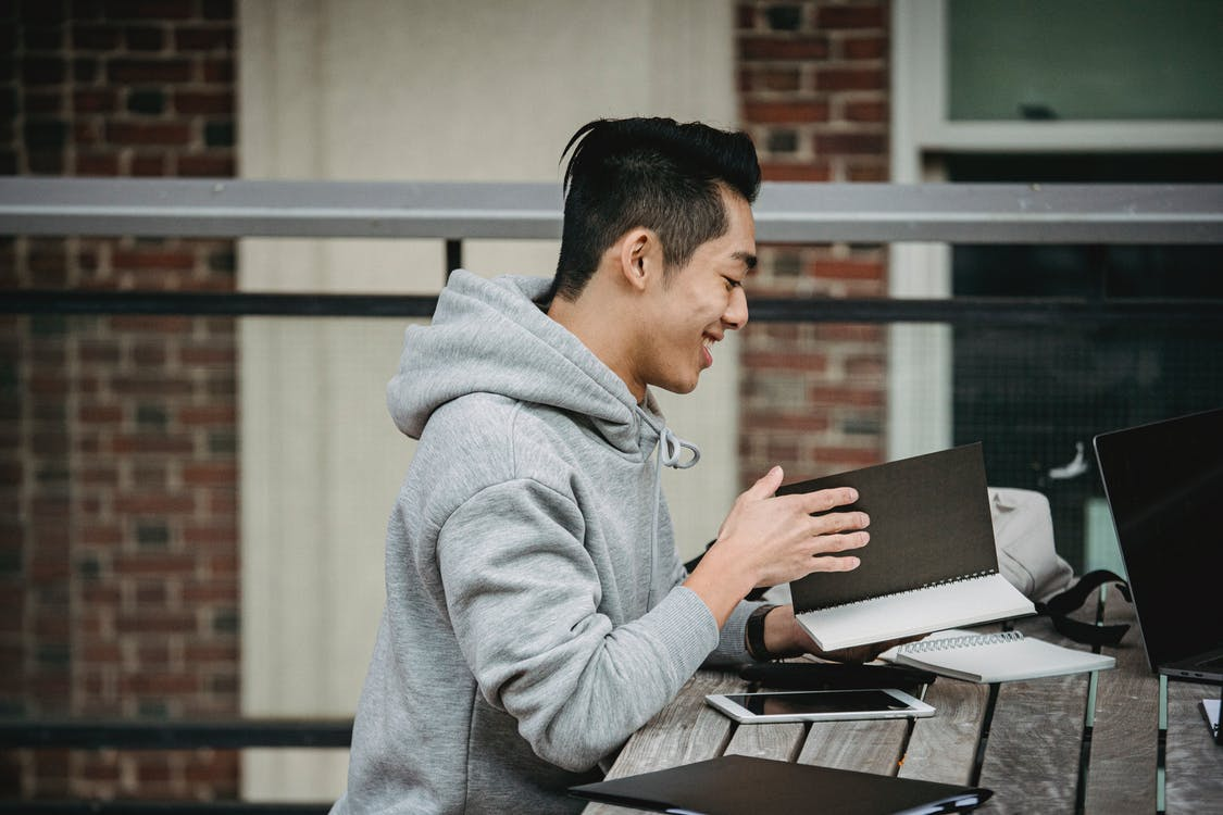Smiling ethnic man with notebook