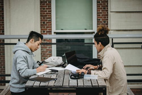 Serious diverse students doing assignment together