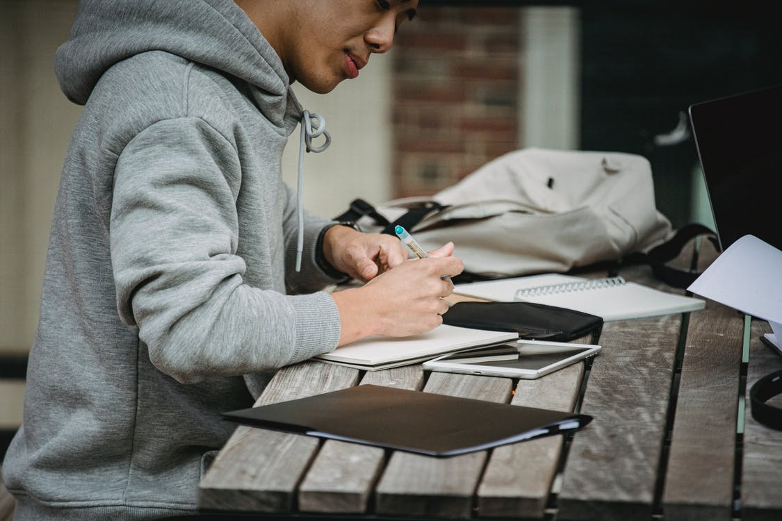 Crop man writing in notebook