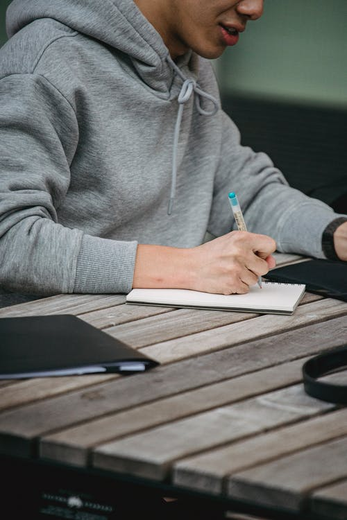 Crop unrecognizable male student in gray hoodie writing notes in notepad while sitting at table and doing homework