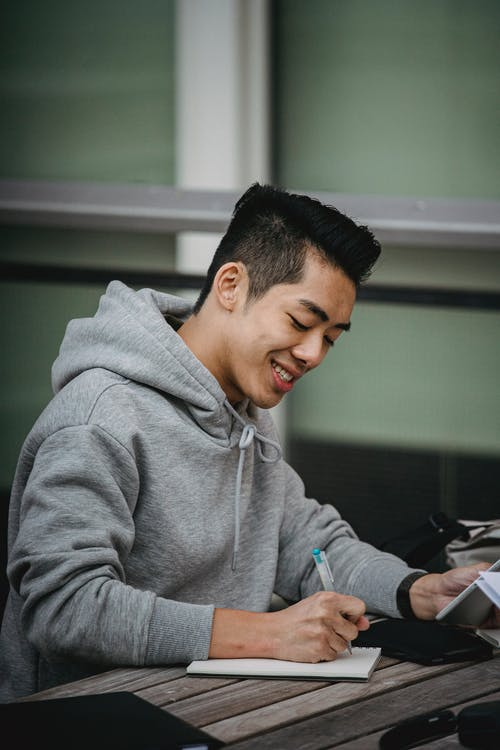Positive young Asian male student taking notes in notepad with tablet in hand while working on project at wooden table