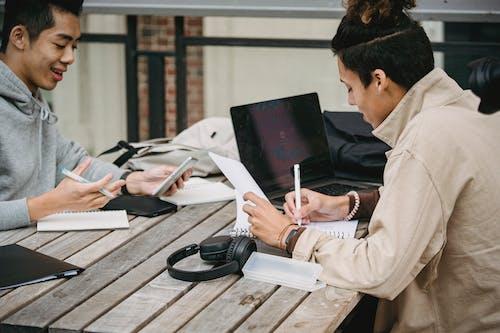 Multiethnic men taking notes in notebooks