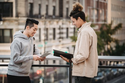 Side view of cheerful young multiracial male friends in casual outfits with tablet and folder with papers discussing new project on street