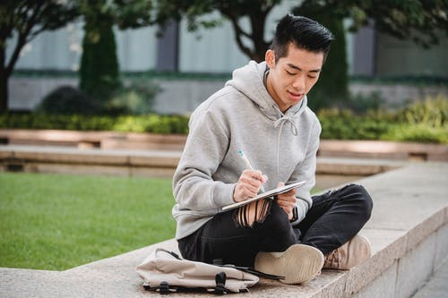 Ethnic man taking notes in notebook