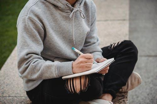Crop man writing in notepad