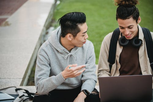 Cheerful young multiracial male friends in casual outfits sitting on stone border and doing and discussing research using laptop