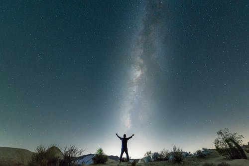 Silhouette of Man Standing on Rock Under Starry Night