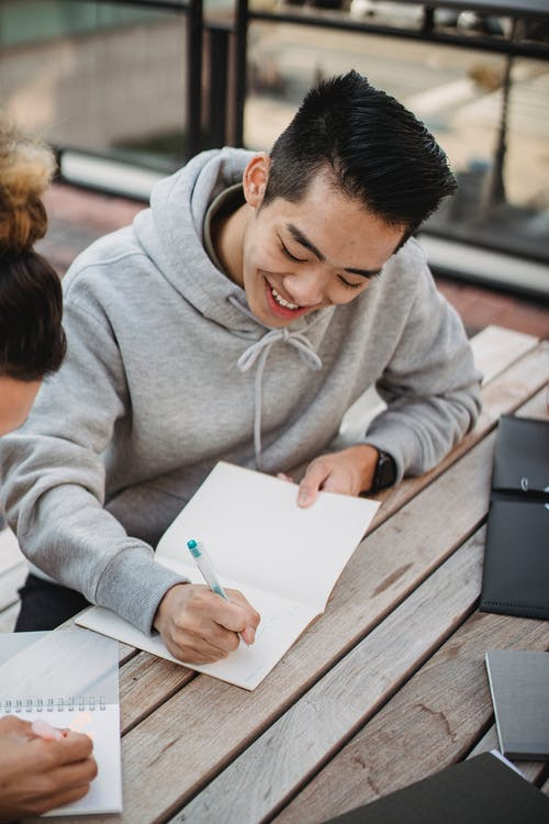 Cheerful Asian male student writing in copybook on terrace
