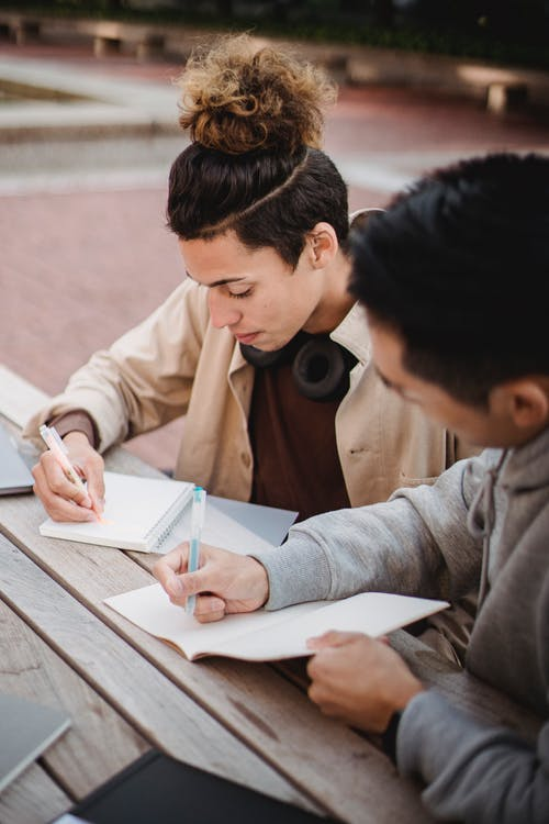 Concentrated male students in casual clothes taking notes in notebooks while preparing for exams together in university campus park