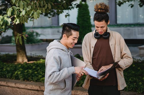 Smiling multiracial male students wearing casual clothes reading article in textbook before seminar while standing in campus park