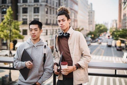 Positive diverse men standing on sunny street