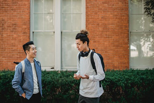Happy multiethnic male friends chatting outside modern building