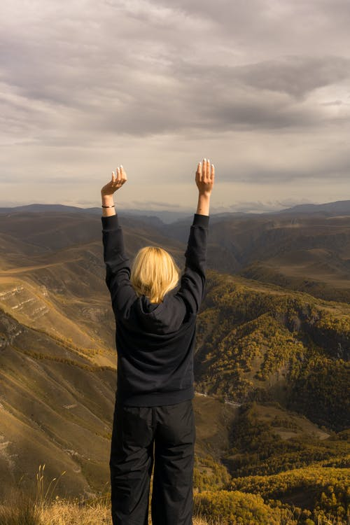Woman standing with raised hands on hilltop