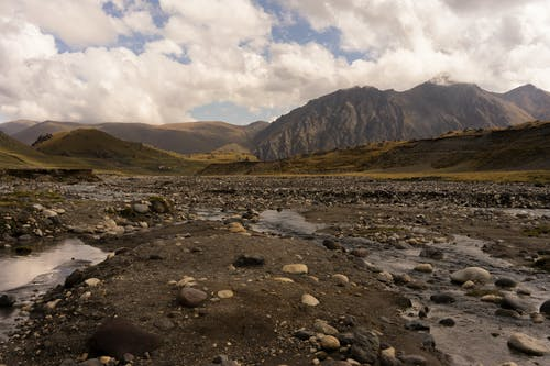 Dried river with rocky coast located near green hills against high mountain in cloudy day