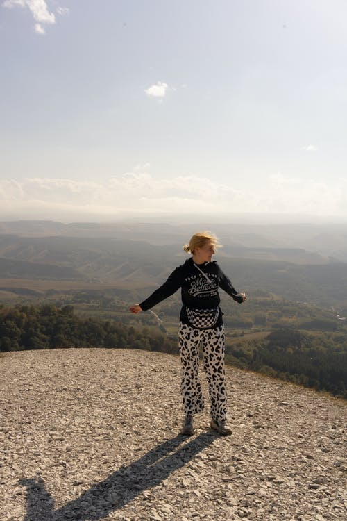 Full body of young female traveler enjoying freedom on rough hill peak over green valley while looking away