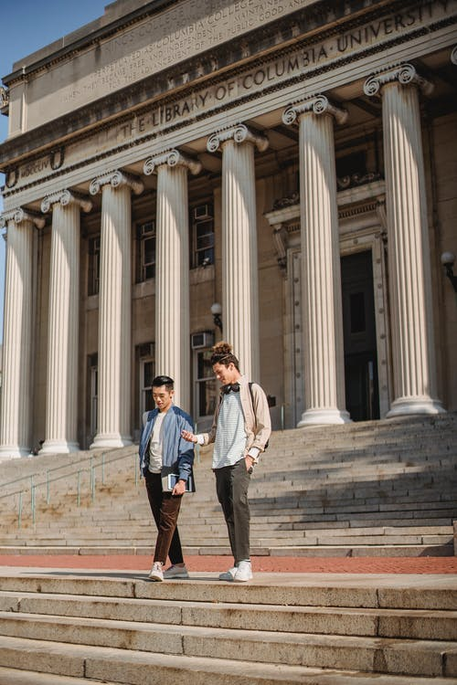 Two Men Standing Outside A University Building