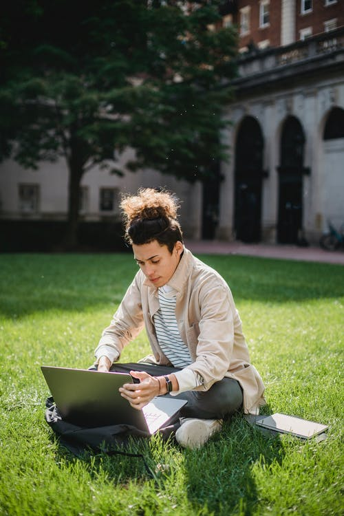 Young student studying with laptop in lawn