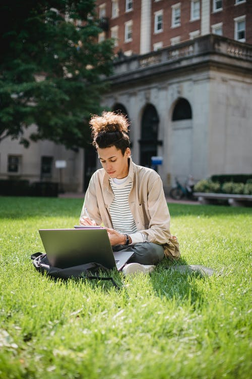 Concentrated male student sitting on green grass while browsing laptop and writing information in notepad
