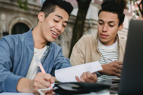 Smiling ethnic male learner writing in document while doing homework assignment with classmate in park