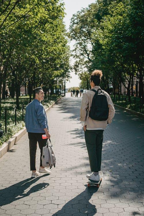 藍色外套和黑色的褲子,在人行道上行走的人