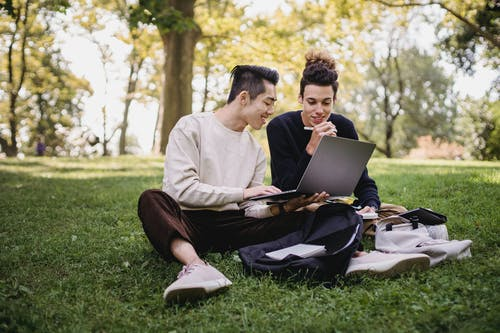 Man in White Dress Shirt Sitting on Green Grass Field Using Laptop Computer