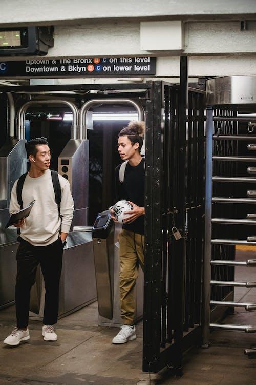 Diverse male students walking through turnstiles in underground