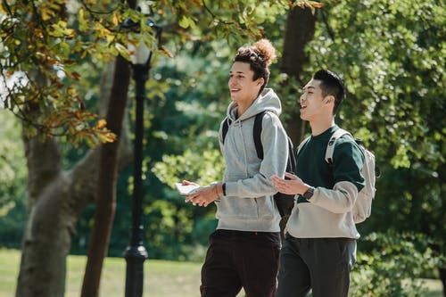 Smiling multiracial friends wearing casual clothes walking in park and talking to each other