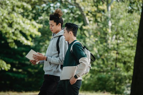 Multiracial students with notebook walking together in park
