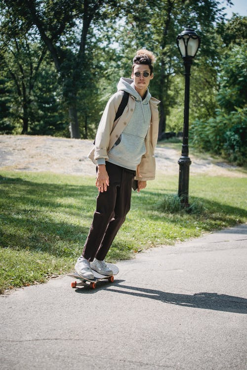 白色禮服襯衫和黑色的褲子,站在灰色的瀝青路上的男人