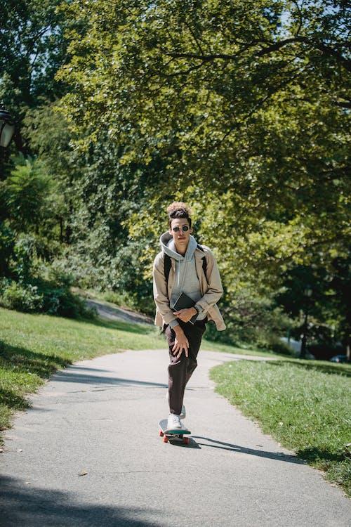 棕色外套和黑色的褲子,站在灰色的混凝土路上的男人