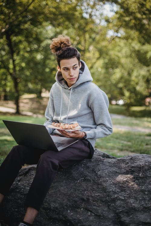 Serious student using laptop and eating pizza