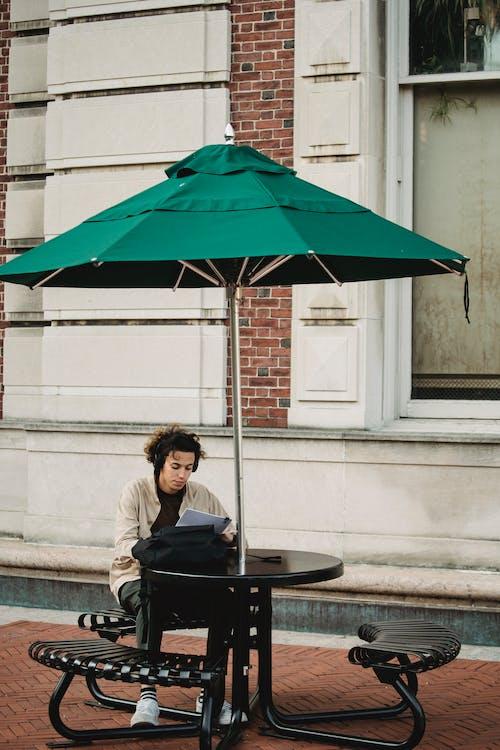 Femme En Veste Noire Assise Sur Une Chaise Noire Sous Un Parapluie Vert