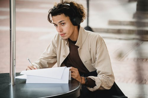 Concentrated male student in wireless headphones sitting at table and writing answers in document during outdoor studies