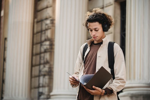 Concentrated male learner in wireless headphones standing against university building and reading documents in folder