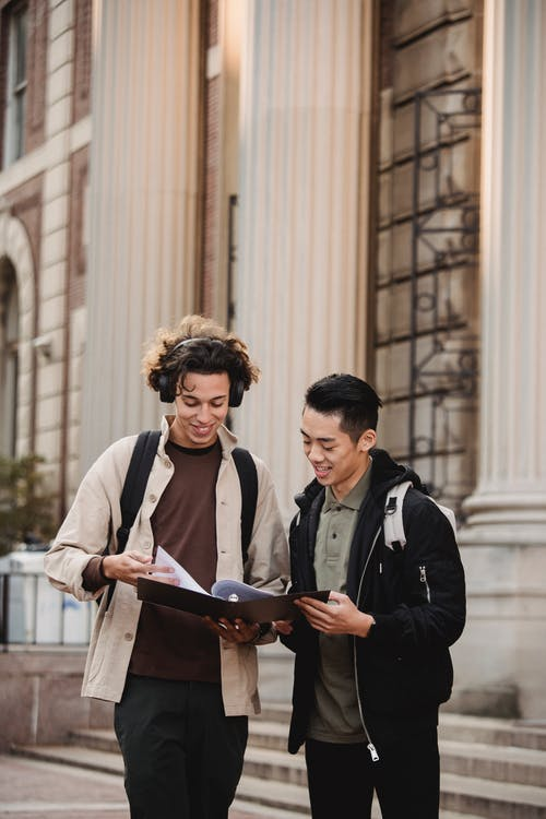Smiling multiracial classmates in casual wear discussing report together standing near  historic university building