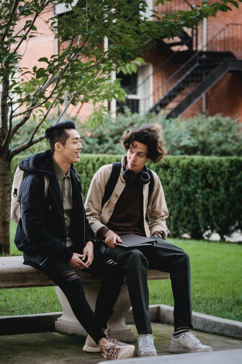Asian man smiling brightly while talking to friend