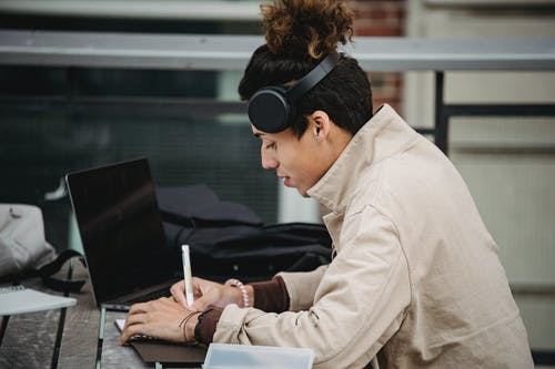 Young ethnic man in headphones taking notes neat laptop