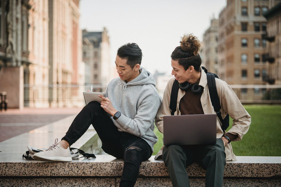 Man and Woman Sitting on Concrete Bench Using Laptop Computers